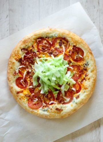 Pizza topped with bacon, lettuce and tomatoes.