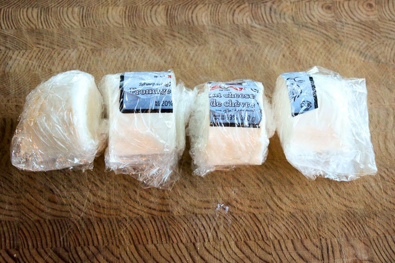 Cut Goat Cheese Log Wrapped in Plastic on Wooden Board.