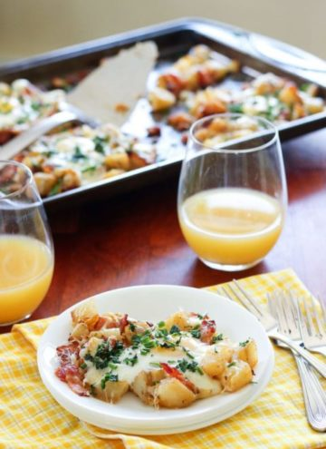 Pan of potatoes, bacon and eggs, with serving on small plate and glasses of orange juice