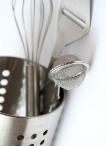 Metal utensils in metal holder.