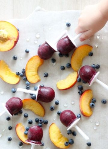 Child reaching for blueberry popsicle next to sliced peaches.