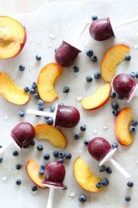 Blueberry peach posicles on wax paper with sliced peaches and blueberries