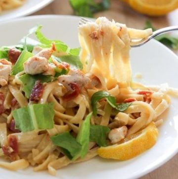 Pasta topped with bacon, chicken and lettuce on white plate.