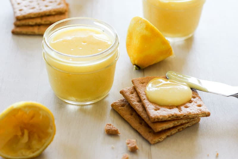 Lemon Curd in Glass Jar and Graham Crackers topped with lemon Curd.
