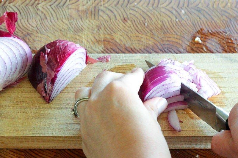 Chopping Red Onion on Wooden Board.