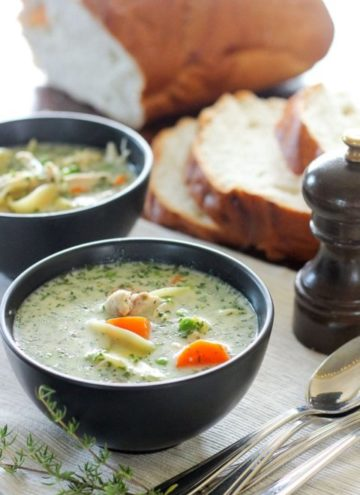 Two black bowls of creamy chicken soup and loaf of bread