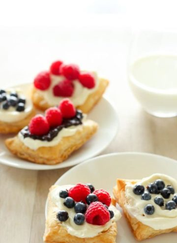Three pastries topped with icing and berries on white plate.