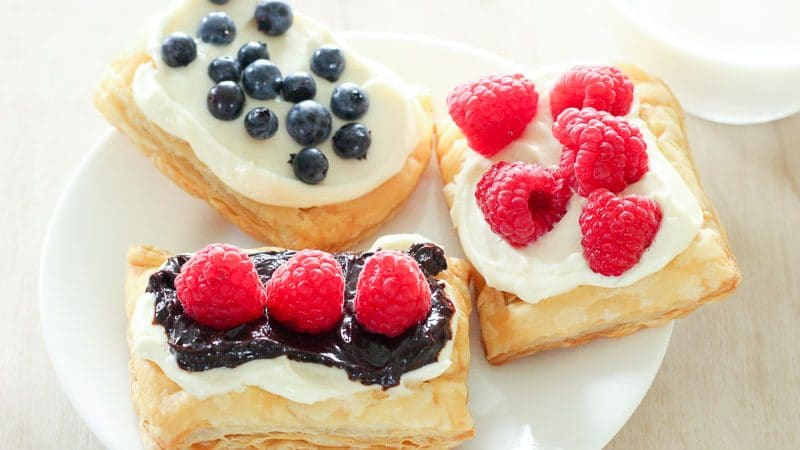 This Easy Berry and Cream Cheese Pastries recipe takes buttery puff pastry, tops it with a rich cream cheese filling and juicy fresh blueberries or raspberries (and chocolate, if you want!). They take about 15 minutes of active time to make and you can make the components ahead of time, making them perfect for breakfast, brunch or dessert! They're the best!