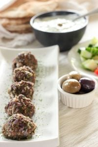 Greek Meatballs topped with parsley in White Rectangular Dish.