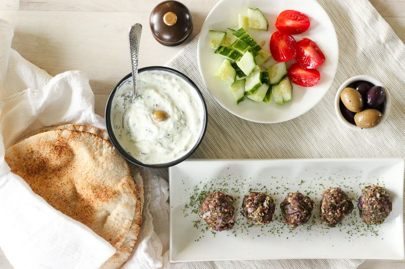 Greek Meatballs on White Rectangular Plate with Vegetables, Bread and Tzatziki.