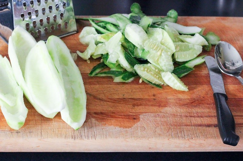 Peeled and Seeded Cucumbers on Wooden Board.