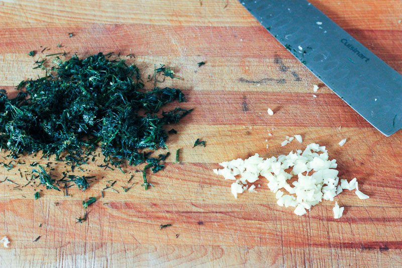Chopped Dill and Garlic on Wooden Board.