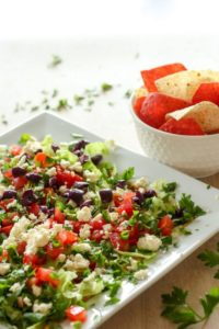 Healthy dip with feta, black olives and other vegetables on white plate.