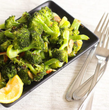 Roasted broccoli in black dish with lemon slice.