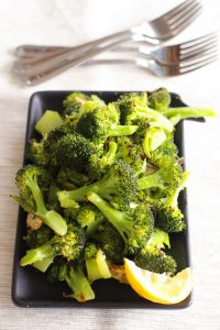 Roasted Broccoli and lemon wedge on black plate.