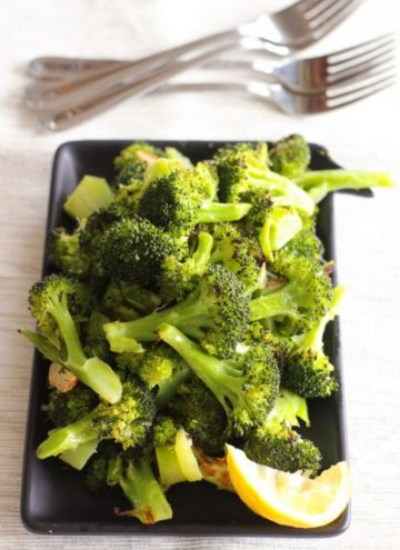Roasted broccoli in black dish with lemon slice.