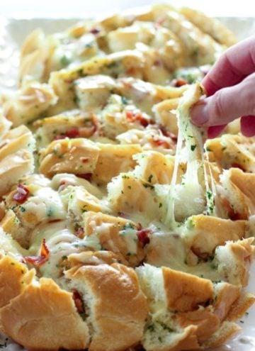 Hand pulling apart cheesy bacon bread.