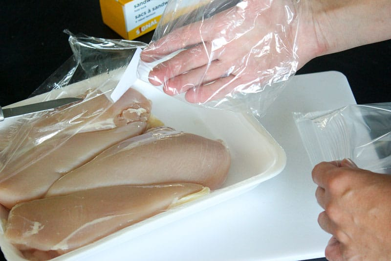 Hand inside Resealable Bag near Raw Chicken Breasts.
