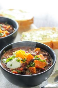 Sweet Potato and Black Bean Chili topped with Sour Cream and Parsley in Black Bowls.