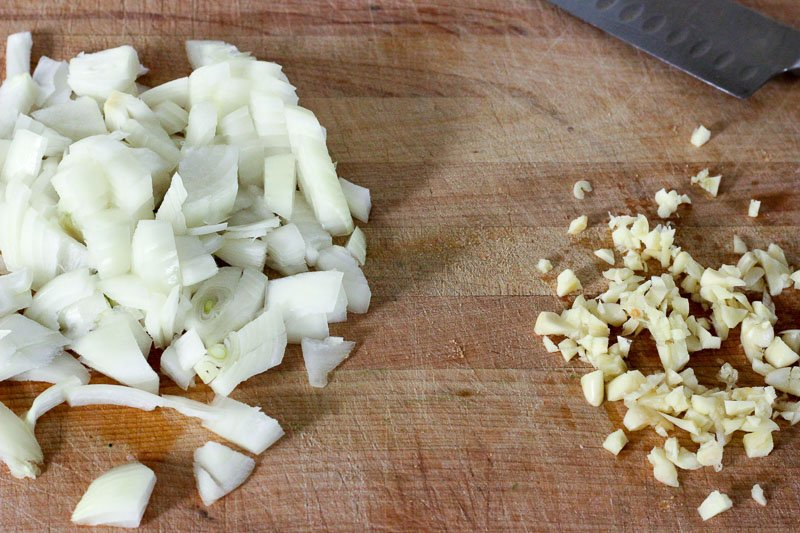 Chopped Onions and Minced Garlic on Wooden Board.