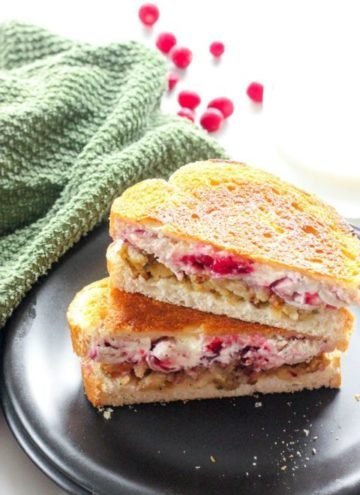Two halves of a grilled sandwich with turkey, cream cheese, stuffing and cranberries, stacked one on top of the other.
