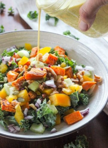 Healthy salad with kale, sweet potato and other vegetables in white bowl.