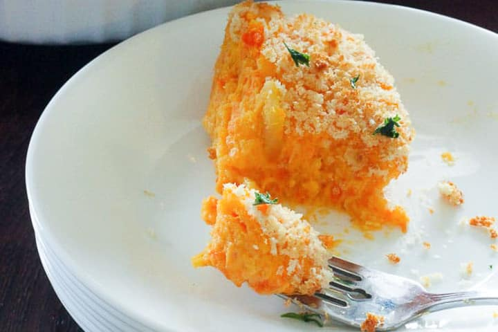 One serving of orange coloured root bake on plate with fork