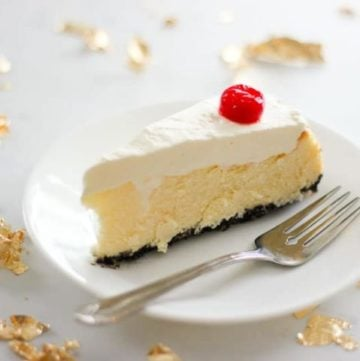 Slice of cheesecake topped with cherry on white plate.