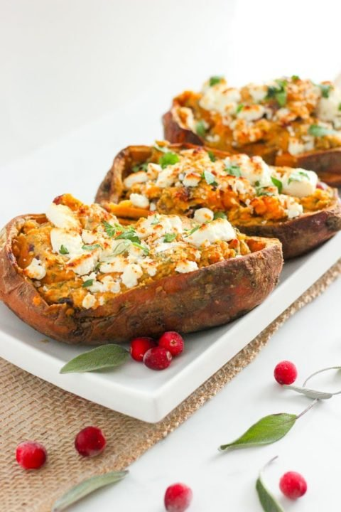 Halved sweet potatoes topped with goat cheese and herbs on white plate.