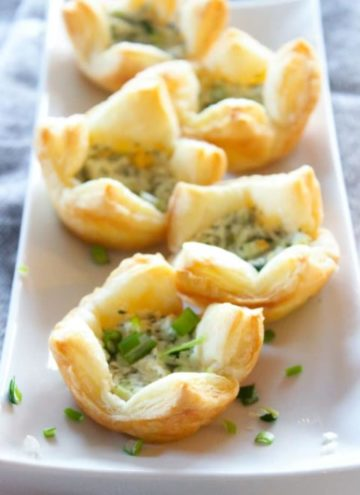 Puff pastries filled with goat cheese and herbs on white plate.