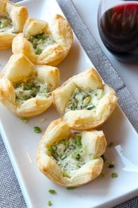 Puff pastry bites filled with herbs and cheese on white plate.