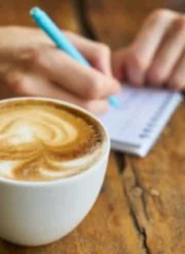 Latte in white mug next to someone writing a list on a notepad.