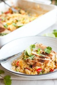 Rice topped with vegetables and sliced chicken in white plate.