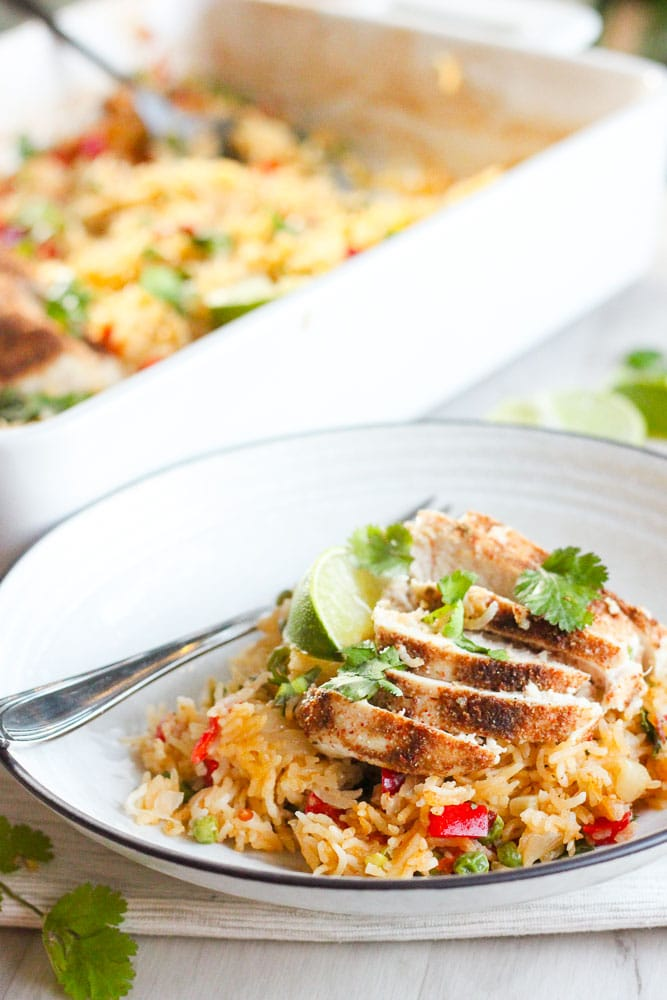 Thai Chicken and Rice Bake topped with Cilantro and Lime Wedge on White Plate.