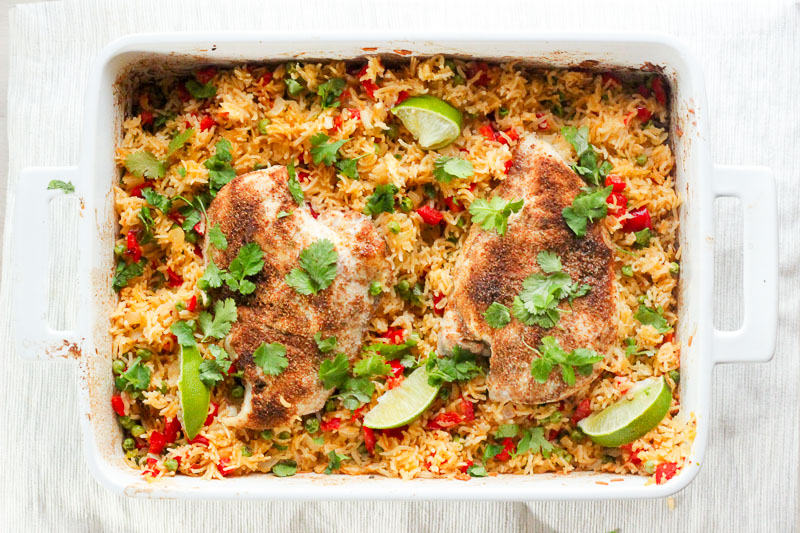 One Pan THAI Chicken and Rice Bake topped with Cilantro and Lime Wedges.