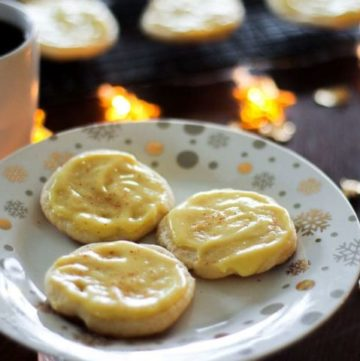 3 soft cookies with yellow icing in white plate.