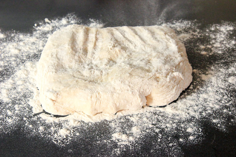 Floured Dough on Black Surface.