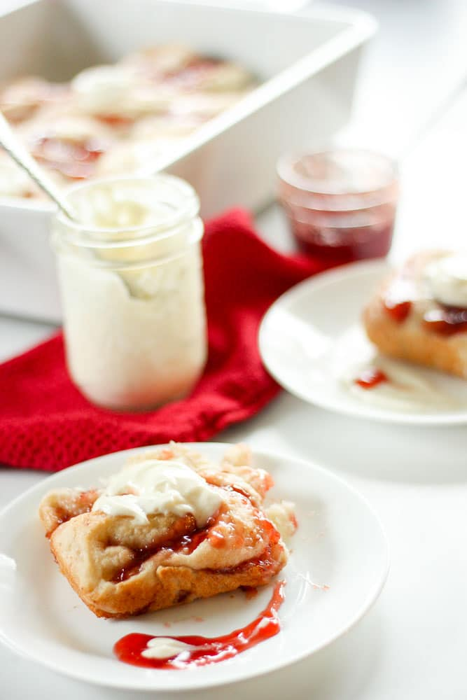 Strawberry Sweet Rolls with Vanilla Cream Cheese Icing on white plate.