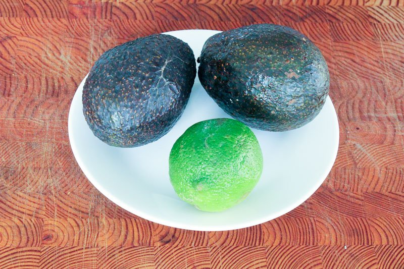 Two Avocados and One Lime on Small White Plate.