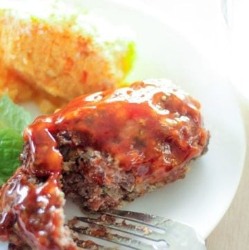 Mini meatloaf, salad and sweet potato on white plate.