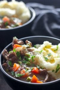 Steak and carrots in gravy with mashed potatoes in black bowl.