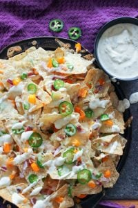 Jalapeño Nachos topped with Garlic Cream Sauce on Black Plate.