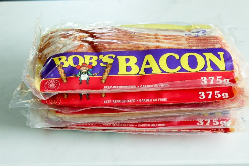 Stack of Packaged Bacon on a White Board.