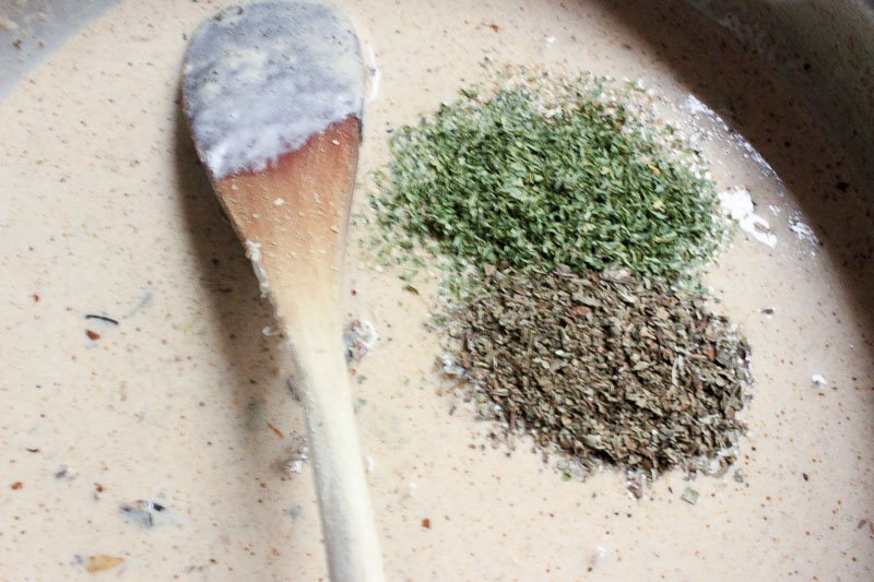 Add herbs to sauce for Creamy Chicken Skillet with Sun Dried Tomatoes and Italian Herbs