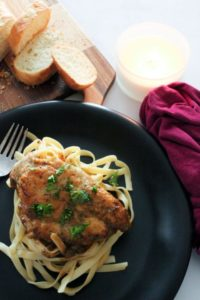Pasta topped with chicken and herbs on black plate.