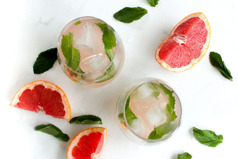 Grapefruit Mint Infused Water in Glasses with Ice Cubes and Mint Leaves.