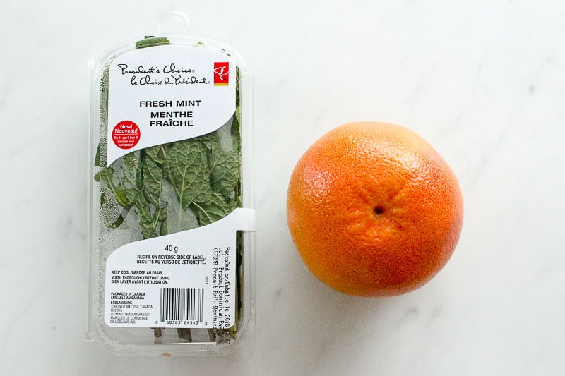 Grapefruit and Package of Mint Leaves on White Marble Board.