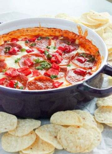 Pepperoni and cheese dip topped with vegetables in a purple dish.