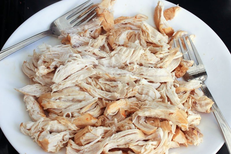 Shredded chicken and two forks on white plate.
