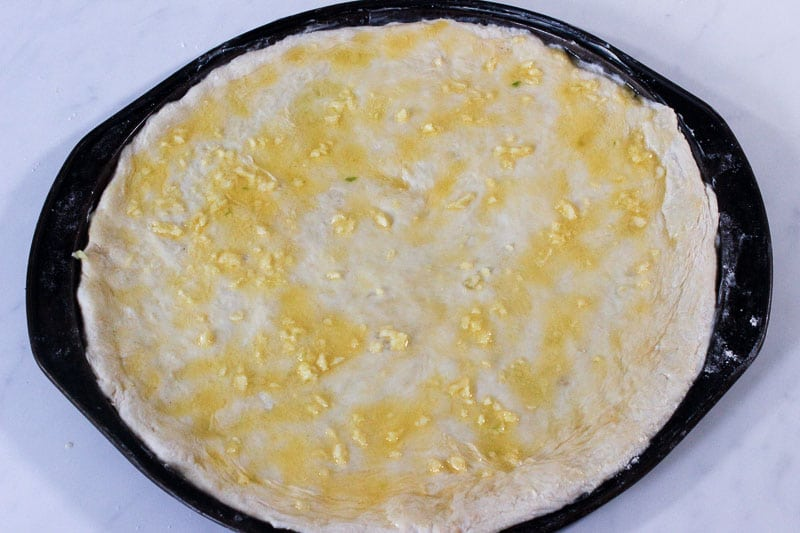 Garlic Butter Spread over Pizza Dough in Round Pizza Pan.